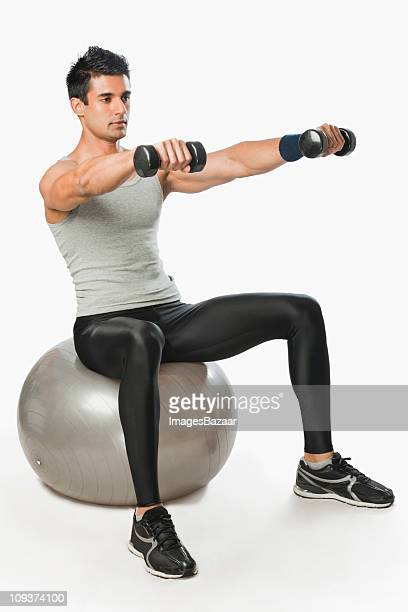 Studio shot of young man exercising on fitness ball
