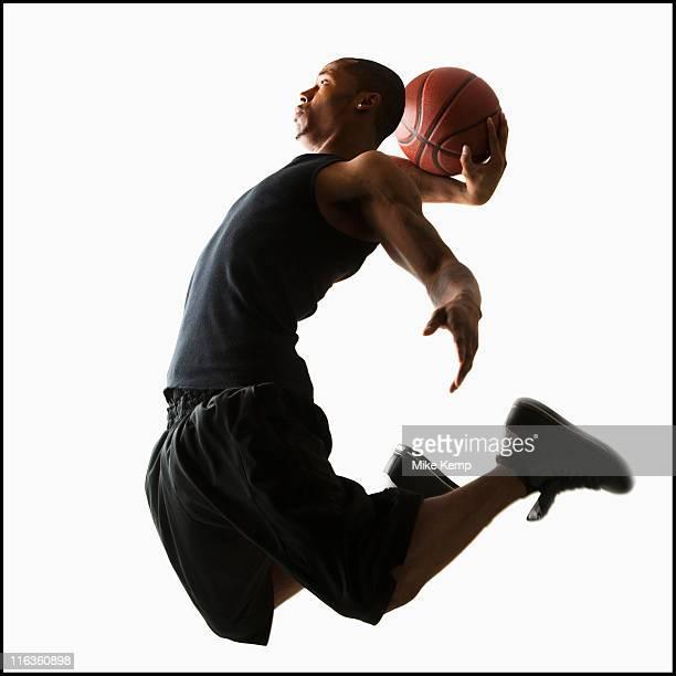 Studio shot of young man playing basketball