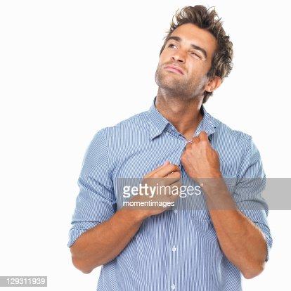 Studio shot of young man unbuttoning shirt