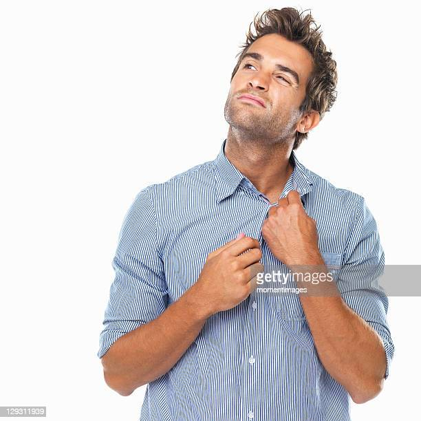 Studio shot of young man unbuttoning shirt