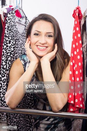 Studio shot of young model choosing dress to wear : Bildbanksbilder