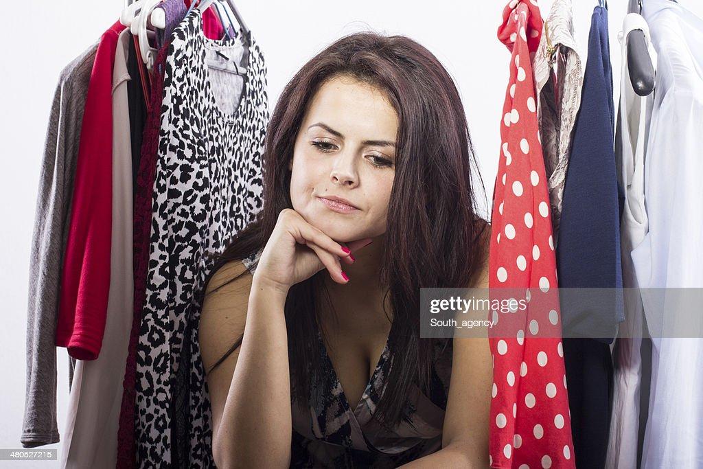 Studio shot of young model choosing dress to wear : Stockfoto