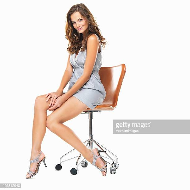 Studio shot of young pretty woman sitting on chair and smiling