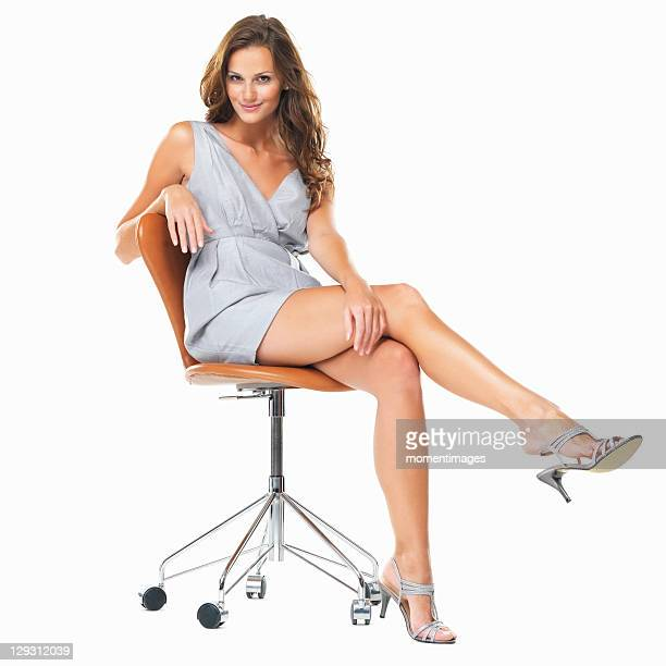 Studio shot of young pretty woman sitting on chair