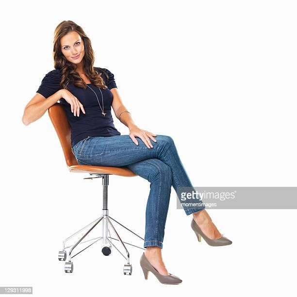 Studio shot of young relaxed woman sitting on chair
