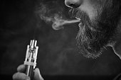 Black and white close-up shot of bearded man holding electronic cigarette in hand and puffing smoke in the air, black background