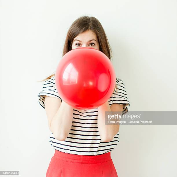 Studio shot of young woman blowing balloon