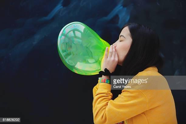 Studio shot of young woman blowing balloon