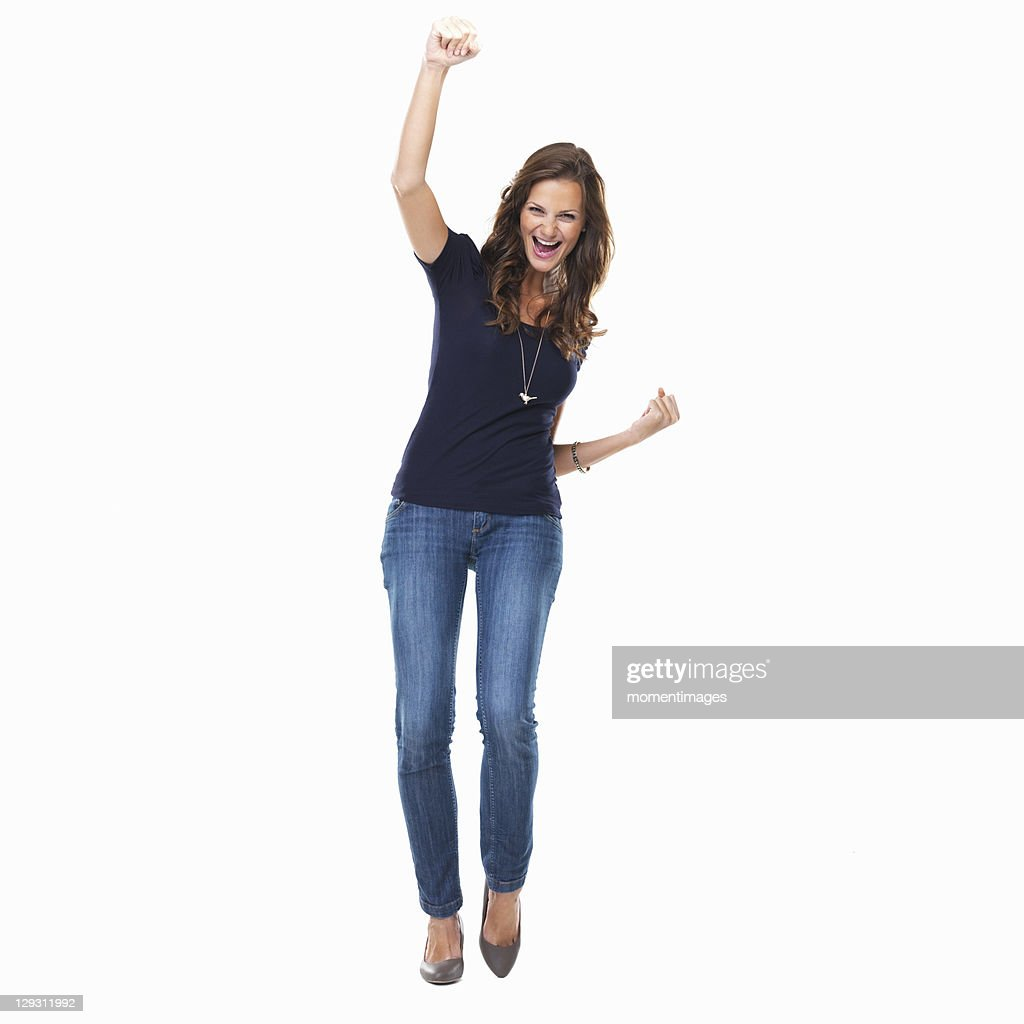 Studio shot of young woman celebrating with arm raised