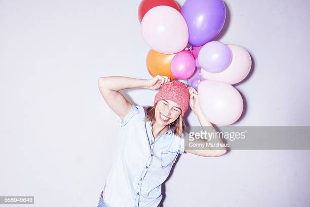 Studio shot of young woman holding bunch of balloons on head