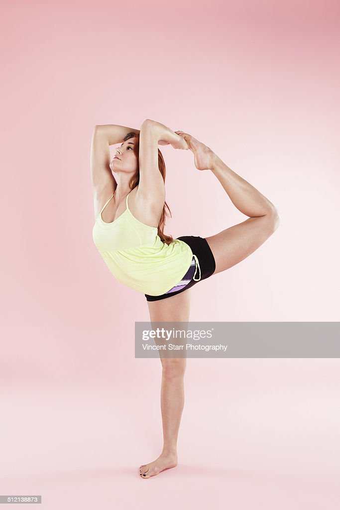 Studio shot of young woman in yoga position bending backwards on one leg touching toes