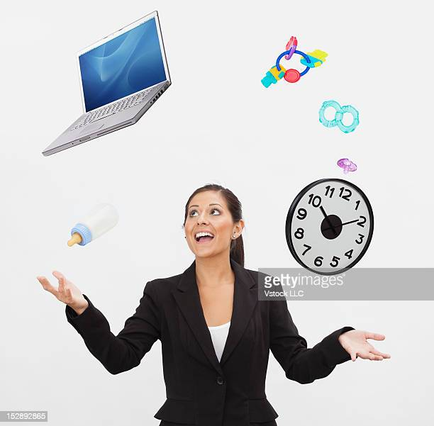 Studio shot of young woman juggling with laptop and baby accessories