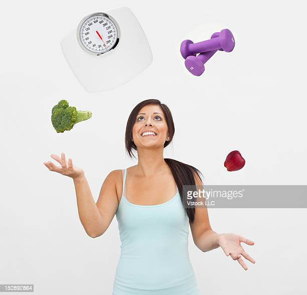 Studio shot of young woman juggling with weight scale, weights, fruit and vegetable