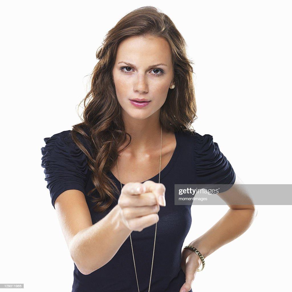 Studio shot of young woman pointing at camera : Stock Photo