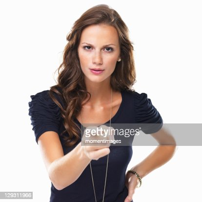 Studio shot of young woman pointing at camera : Stock Photo