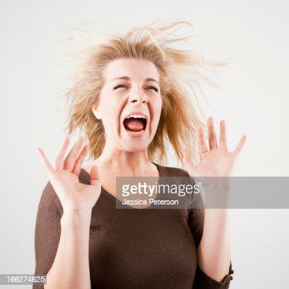 Studio shot of young woman screaming