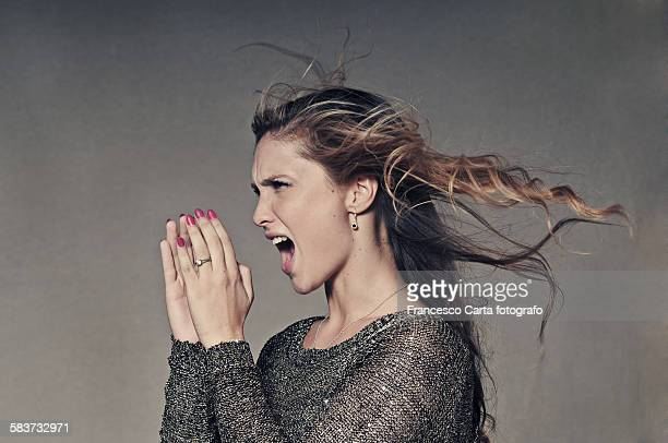 Studio shot of young woman shouting