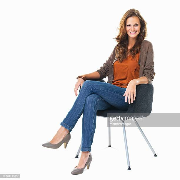 Studio shot of young woman sitting in chair