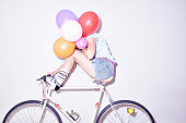 Studio shot of young woman sitting on bicycle hiding behind bunch of balloons