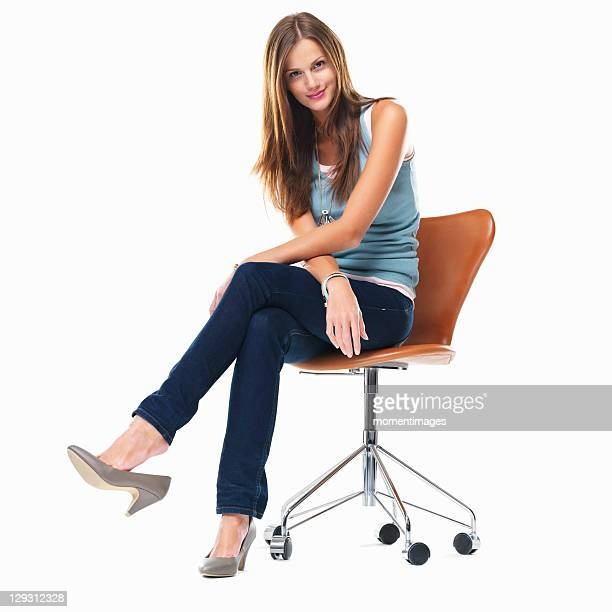 Studio shot of young woman sitting on chair with legs crossed
