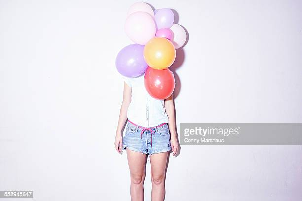 Studio shot of young woman standing behind bunch of balloons