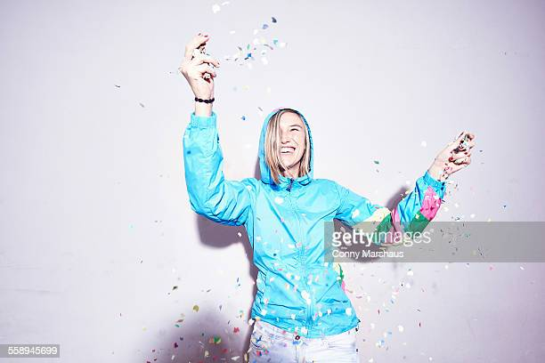 Studio shot of young woman throwing confetti