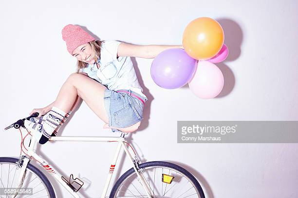 Studio shot of young woman with feet up on bicycle holding bunch of balloons