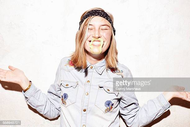 Studio shot of young woman with mouth covered in yellow gum bubble