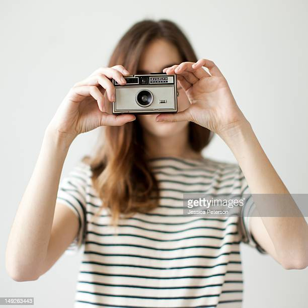Studio shot of young woman with old-fashioned camera