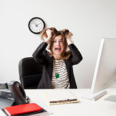 Studio shot of young woman working in office and tearing her hair out