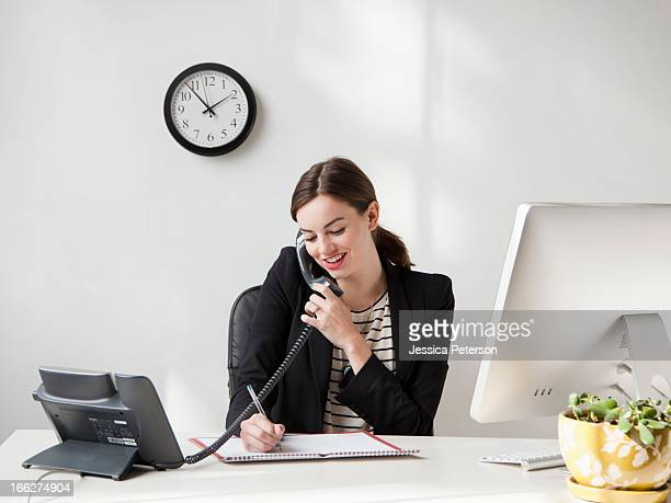 Studio shot of young woman working in office talking on phone