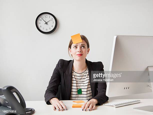 Studio shot of young woman working in office with adhesive note on her forehead