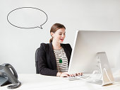 Studio shot of young woman working on computer with speech bubble next to her head