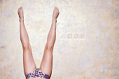 Studio shot of young womans bare legs upside down against wall