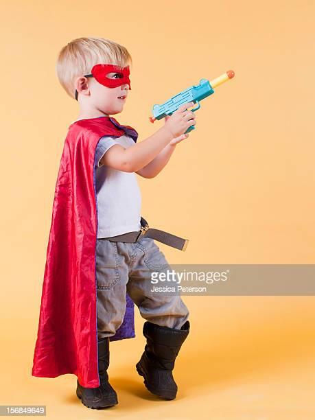 Studio shot, Portrait of boy (2-3) wearing cape and holding toy gun.
