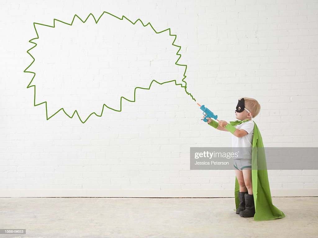 Studio shot, Portrait of boy (2-3) wearing green cape and holding his toy gun. : Stock Photo