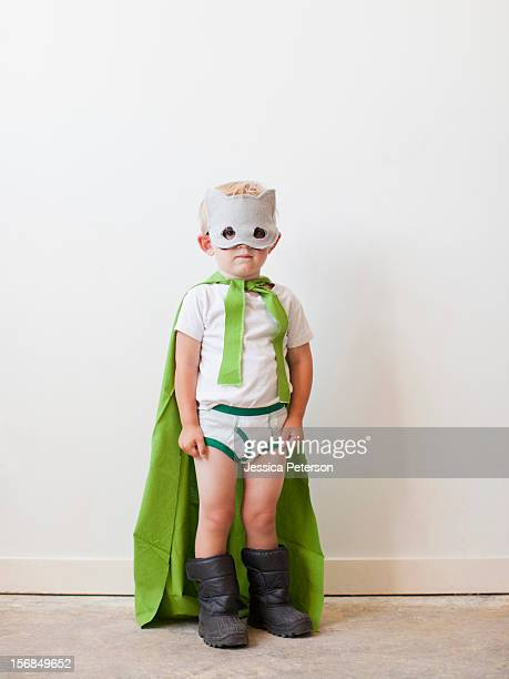 Studio shot, Portrait of boy (2-3) wearing green cape and mask.
