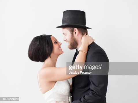 Studio Shot portrait of bride and groom smiling face to face : Stock Photo