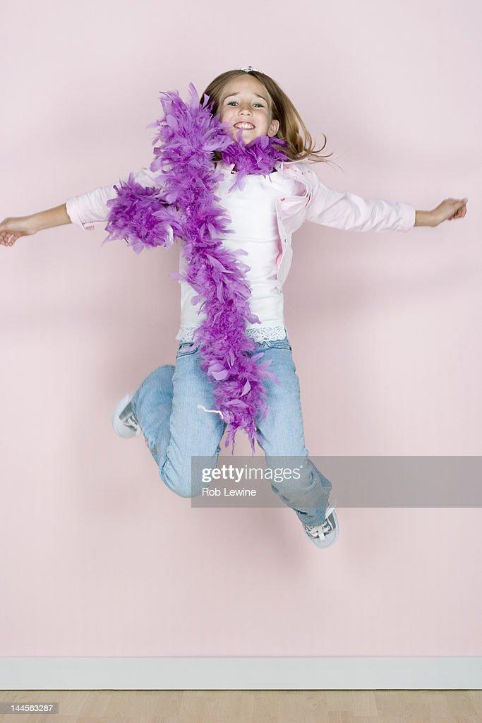 Studio shot portrait of jumping teenage girl in feather boa shawl, full length