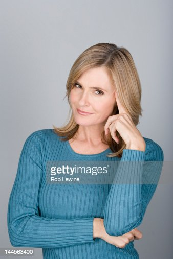 Studio shot portrait of mature woman with hand on chin, head and shoulders