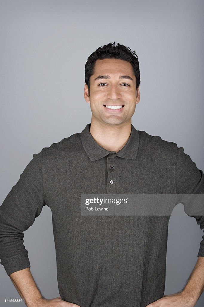 Studio shot portrait of mid adult man with hands on hip, waist up
