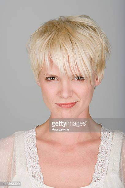Studio shot portrait of mid adult woman with tousled hair, close-up