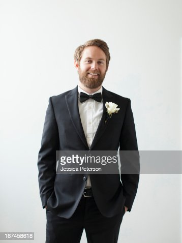 Studio Shot portrait of smiling groom with hands in pockets