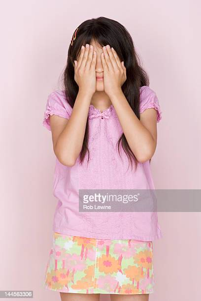Studio shot portrait of teenage girl covering face, three quarter length