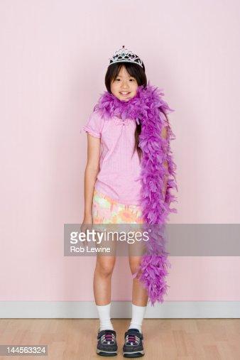 Studio shot portrait of teenage girl in diadem and feather boa shawl, full length