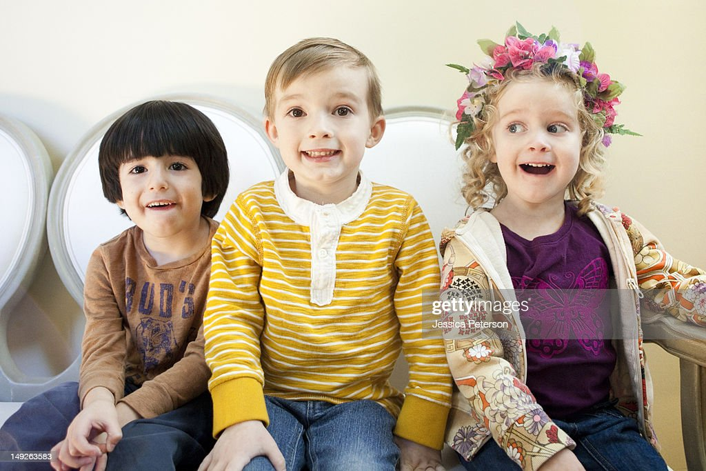 Studio Shot portrait of three children (4-5, 6-7) sitting side by side : Stock Photo