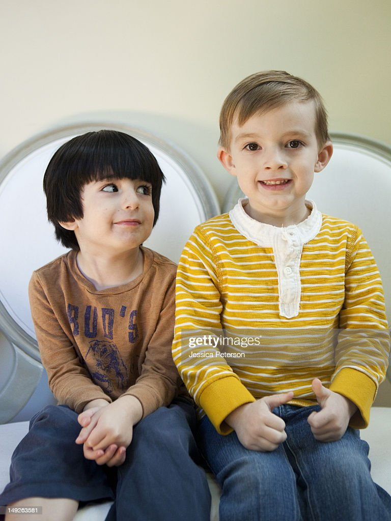 Studio Shot portrait of two boys (4-5, 6-7) sitting side by side : Stock Photo