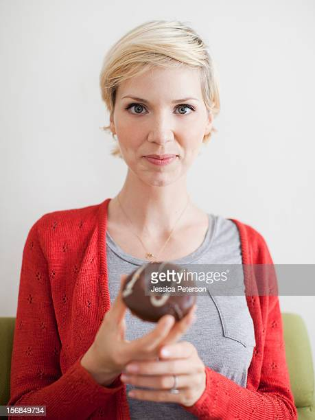 Studio shot, Portrait of woman holding chocolate covered doughnut.