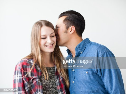 Studio Shot portrait of young couple whispering and smiling : Stock Photo