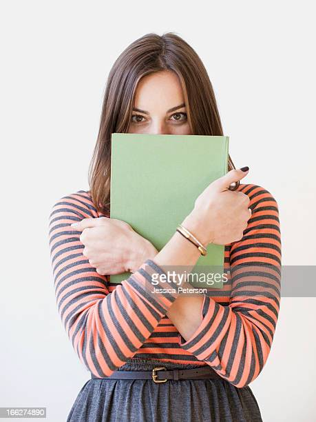 Studio shot portrait of young woman holding book